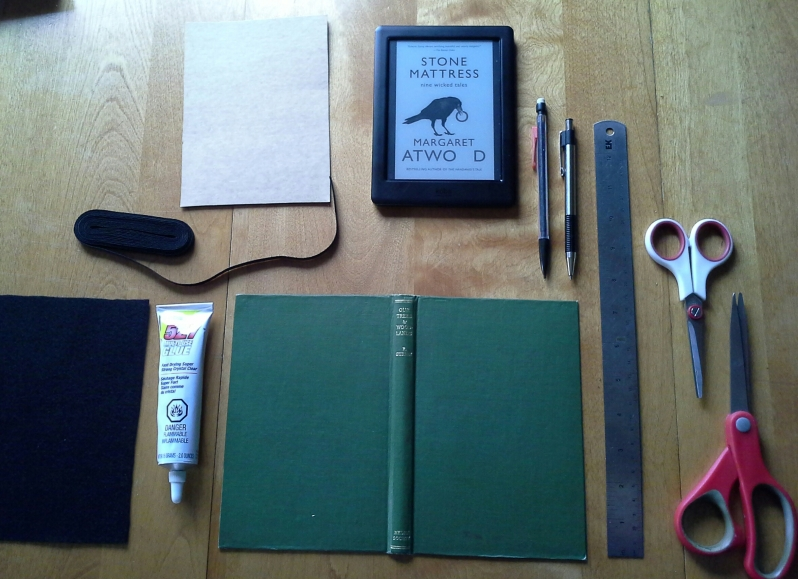 Materials: an old book cover, some cardboard, felt, elastic, scissors, ruler, glue.